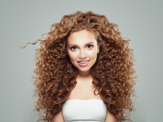 Perfect redhead girl with long healthy curly hair. Hair care concept