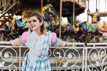 Sensual street artist standing near carrousel