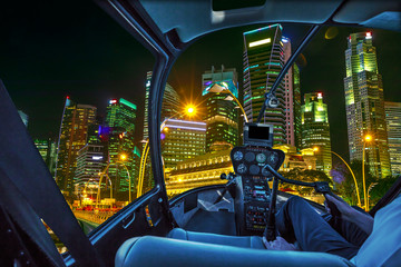 Helicopter interior on Singapore financial buildings and skyscrapers of downtown reflected in the sea of the harbor. Scenic flight above Singapore skyline by night in marina bay promenade waterfront.