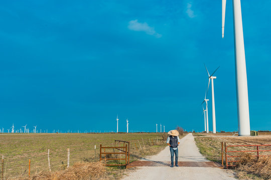 A cowboy standing in front of the wind turbines, travel