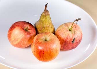 pommes et poire sur assiette gros plan