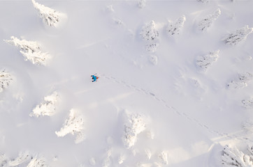 Sunny winter landscape with man on snowshoes, aerial view.