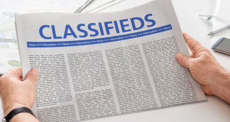 Man reading newspaper with the headline Classifieds