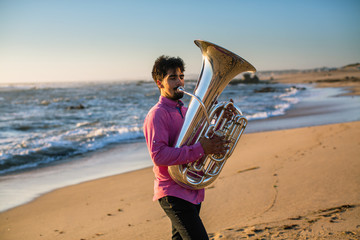 Musician play to tuba on the Sea shore.