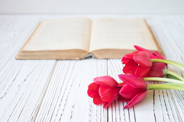 old book and tulips on white wooden table