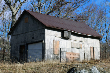 Old rustic weathered wooden barn abandoned in New England Village