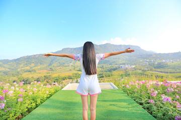 Back of young Asian woman feeling free with arms wide open at beautiful trees and mountains on blue sky with morning sunlight.