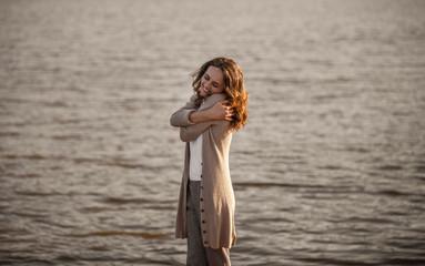 Woman embracing herself near water
