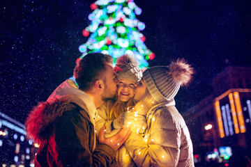 family, christmas, holidays, season and people concept - happy family over lights city background and snow at night Fotomurales