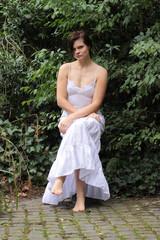 Frau im weißen Kleid vor grüner Hecke