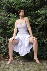 Frau mit gespreizten Beinen im Sommerkleid sitzend