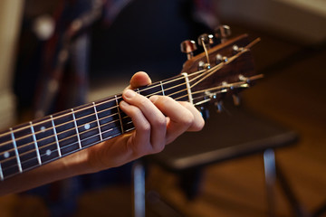 man playing guitar and holding a chord