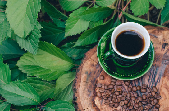 A cup of coffee on a cut tree with coffee beans and leaves.