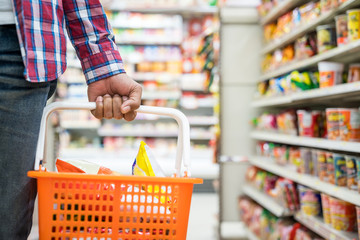 Men's hand holding basket in the supermarket, Grocery shopping concept.