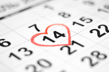 Valentines day and Holidays concept - Calendar sheet with 14th february date marked by red heart shape. Close up