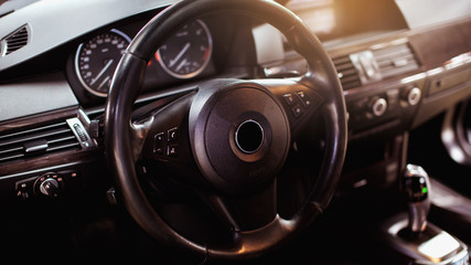 Steering wheel in a new car. Steering wheel with control buttons. Modern car interior in black color.
