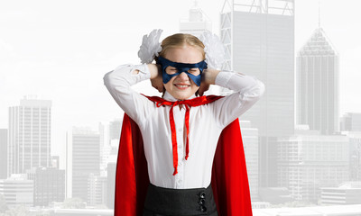 Kid girl superhero against cityscape background annoyed by city sounds