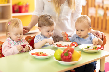 group of kids eating from plates in day care centre