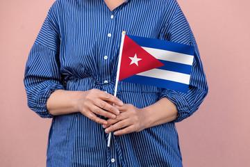 Cuba flag. Close up of a woman's hands holding Cuban flag.