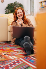 Laughing woman on the floor with laptop