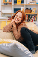 Young woman giggling, sitting on couch at home
