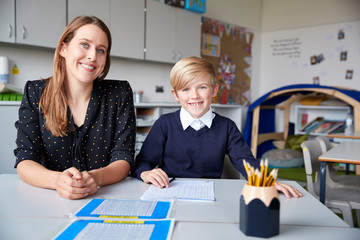 Young female primary school teacher and schoolboy sitting at a table, working one on one in a classroom, smiling to camera, front view, close up