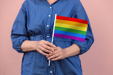 LGBT flag. Close up of a woman's hands holding rainbow flag.