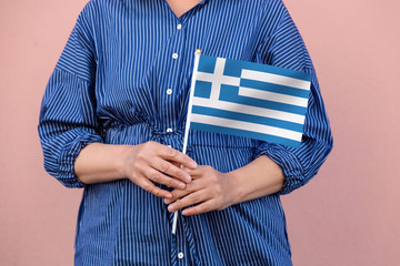 Greece flag. Close up of woman's hands holding Greek flag.