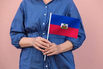 Haiti flag. Close up of woman's hands holding Haitian flag.