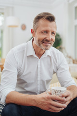 Man sitting relaxing with a mug of coffee