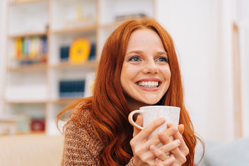 Vivacious young woman enjoying a cup of coffee