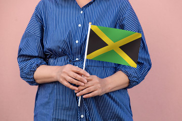 Jamaica flag. Close up of woman's hands holding Jamaican flag.