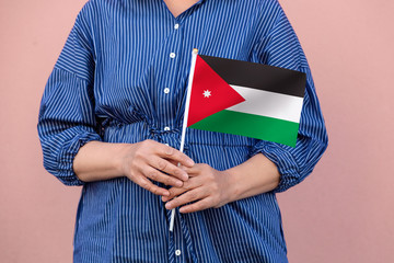 Jordan flag. Close up of woman's hands holding Jordanian flag.
