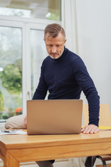 Man sitting on desk and looking at laptop
