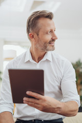 Businessman holding a tablet looking aside