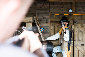Blurry Man at Foreground Aiming at Clear Ranch Themed Items with Bulls Eye Tag. Male Cowboy Human Dummy Holding a Gun. Bokeh Blur Effect in Taking Picture