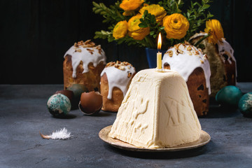 Traditional Russian Easter cottage cheese dessert, Orthodox Paskha with burning candle standing in ceramic plate on dark texture table with kulich cakes, flowers, colored eggs. Rustic style.