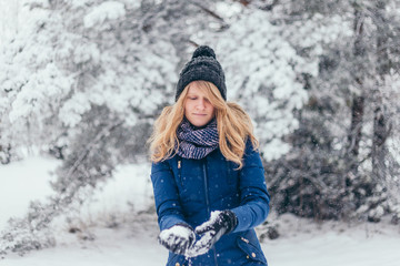 Close-up of happy cute attractive girl in woolen scarf enjoying winter moments - outdoor of long-haired blonde laughing lady in knitted hat having fun in snowy day on blurred nature forest background