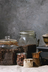 Coffee collection. Roasted black coffee beans in jar, vintage coffee grinder, jezve pot, cream jug, sweet sugared almond standing on table with linen table cloth.