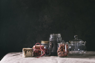 Tea collection. Black dry tea in jar, rose buds, empty glass teapot, cream jug, sweet sugared almond standing on table with linen table cloth.