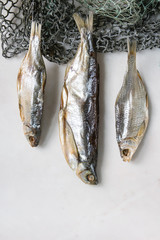 Dried fish or stockfish on fishing nets over white marble background. Flat lay, space