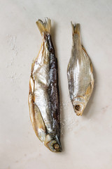 Dried fish or stockfish over white marble background. Flat lay, space