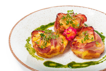 plate of bacon wrapped scallops in neat rows on a light colored plate