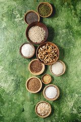 Variety of raw uncooked grains superfood cereal chia linen, sesame, mung bean, walnuts, tapioca, wheat, buckwheat, oatmeal, coconut, rice in wooden bowls over green texture background. Flat lay, space