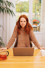 Young red-haired woman leaning on table