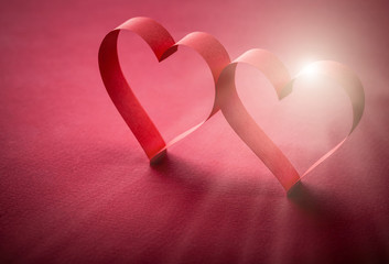 two beautiful romantic heart, made of paper tape in the rays of light on a red paper background - pictures concept theme love and St. Valentine's Day
