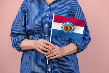 Missouri state flag. Close up of woman's hands holding Missouri flag.