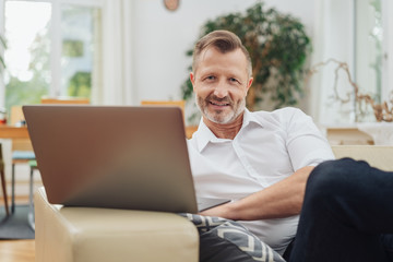 Mature bearded man relaxing with a laptop