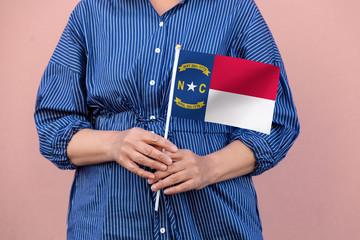 North Carolina flag. Close up of woman's hands holding North Carolina flag.