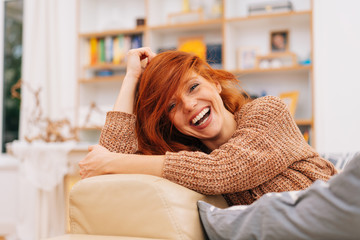Laughing happy young woman relaxing on a sofa